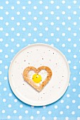A fried quail's egg baked into a heart-shaped slice of toast