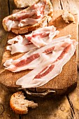 Rashers of bacon and slices of bread on a chopping board