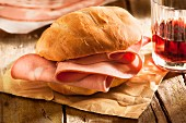 A mortadella roll on a piece of paper