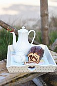 Marble cake and coffee on a tray on a wooden bench in a garden