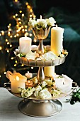 Lit candles and white roses on cake stand