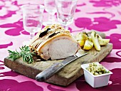 Crispy roast pork with rosemary potatoes on a wooden board