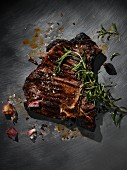 A grilled T-bone steak with rosemary, marinade and garlic