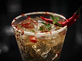 A champagne drink with chilli and ice cubes garnished with a chilli pepper and herbs in glass with a white chocolate rim