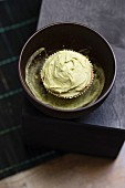 A cupcake with matcha tea frosting in a bowl on matcha powder