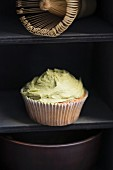 A cupcake with matcha frosting, a matacha bowl and a matacha whisk on a shelf