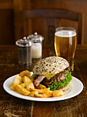 A hamburger with chips and beer in a pub