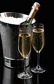 Two glasses of champagne in front of an ice bucket with a bottle of champagne in it