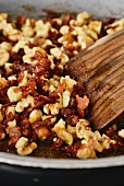 Roughly chopped walnuts being roasted with bacon