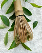 A tea whisk with tea leaves