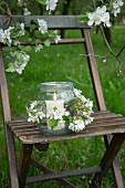 A candle holder on a chair decorated with apple blossom