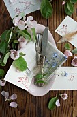 Silver cutlery, flowers and Easter place cards in dish