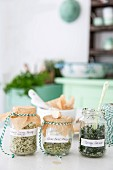 Three different home-made herb salts in storage jars