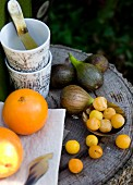 Fresh fruit and stacked beakers on tree stump table outside