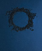 A ring of tea leaves on a dark blue surface