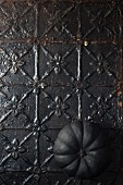 Black pumpkin on metal surface