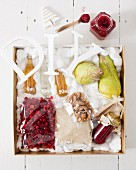 Pear, walnut and cranberry sauce in a jar with ingredients in a gilded crate