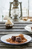 Homemade chocolate truffles on an old wooden table in front of a window