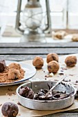 Homemade chocolate truffles with ingredients on an old wooden table in front of a window