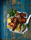 Grilled hickory peri-peri chicken with mango and parsley on a piece of paper
