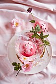 Champage with rose syrup, ice cubes and pink pepper
