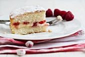 A slice of Victoria sandwich cake with raspberries