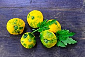 Pattypan squash with leaves on a wooden surface