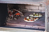 Two pizzas in a pizza oven