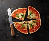 A tomato, mozzarella and basil pizza, sliced