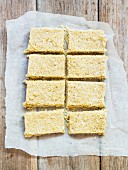 Vegan coconut slices on a piece of baking paper (seen from above)