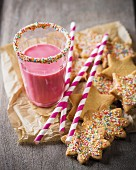 Butter biscuits with colourful sugar sprinkles next to a strawberry milkshake