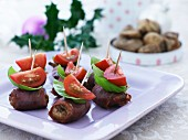 Meatballs wrapped in ham with basil and tomatoes on sticks