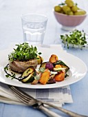 A beef burger wrapped in bacon topped with fresh herbs and served with oven-roasted vegetables