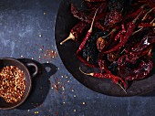 Dried chilli Peppers and chilli flakes in bowls (seen from above)