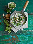 Green Thai curry with chicken breast fillet and kale in a pan