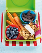 Muesli bars, blueberries and carrots in a lunch box