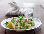 Pasta with a creamy sauce, ham, peas, parsley and lemons