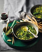 Green vegetable soup with pesto and breadsticks