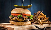 A luxury hamburger with bacon, lettuce, tomatoes, onions, fried mushrooms, Emmental cheese and Cheddar cheese