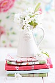 Cherry blossom in ceramic vase on stacked tea towels