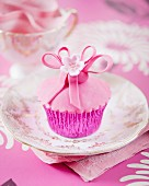 A pink flower cupcake on a gilded plate