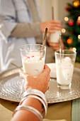 A woman holding a glass of Christmas dessert