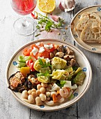 Italian appetiser platter served with bread and red wine
