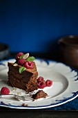A slice of dark chocolate cake with raspberries, mint and liquid cream