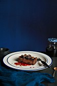 A slice of dark chocolate and cherry tart on a white plate with a blue rim and fork