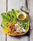 A summer salad platter with cos lettuce, chick peas, carrots, celery, feta cheese and a mustard vinaigrette