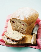 Sliced cranberry and walnut bread on a chopping board