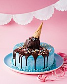 A children's birthday ice cream cake with blue butter cream, an ice cream cone and chocolate
