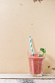 A glass of strawberry smoothie with chia seeds and fresh mint