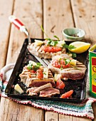 Grilled tuna fish steaks with pineapple and citrus fruits